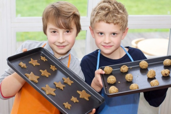 Image of two kids with baking sheets