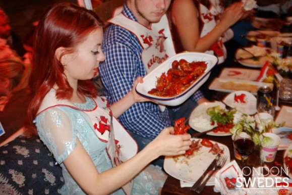 Image of young woman serving herself crayfish